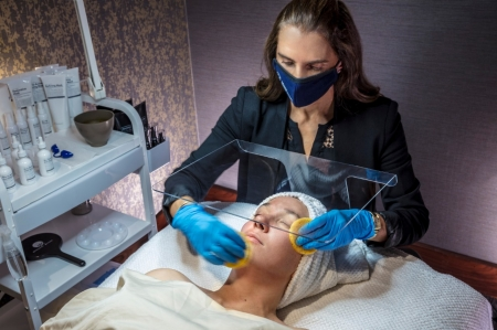 An aesthetician performs a facial on a relaxed female client.