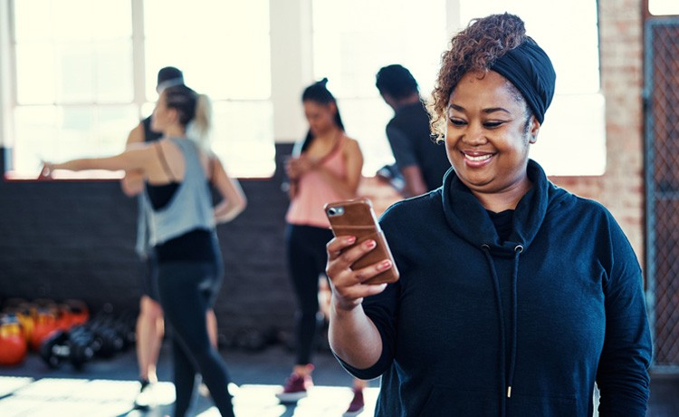 Woman checks phone during fitness class