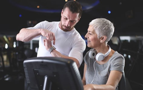 Trainer shows fitness tracker to woman on treadmill