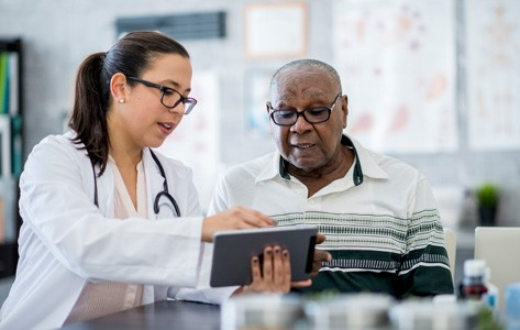 doctor shows cancer resources to patient on tablet