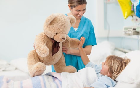 Child life specialist hands teddy bear to sick child