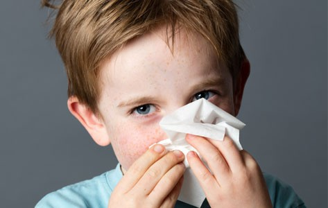 Child with allergies blows nose