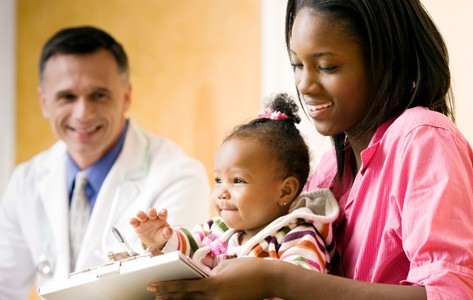 Mother reviews pediatric resources with doctor