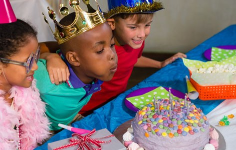 Kids blow out candles on a birthday cake