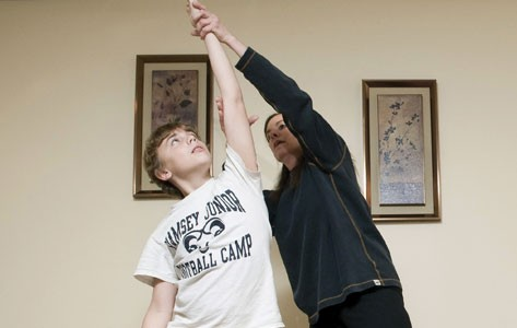 Physical therapist helps child stretch arm