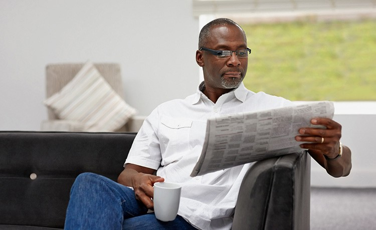 African American man reads newspaper
