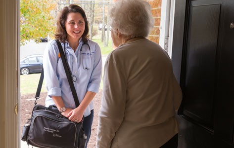 Visiting nurse greets patient at the door