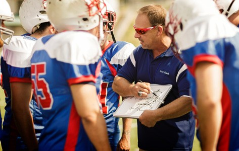 youth football coach explains the play to his players