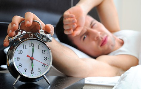 Man with sleep disorder reaches for alarm clock