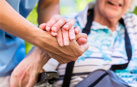 A home health aide holds the hand of an elderly woman.