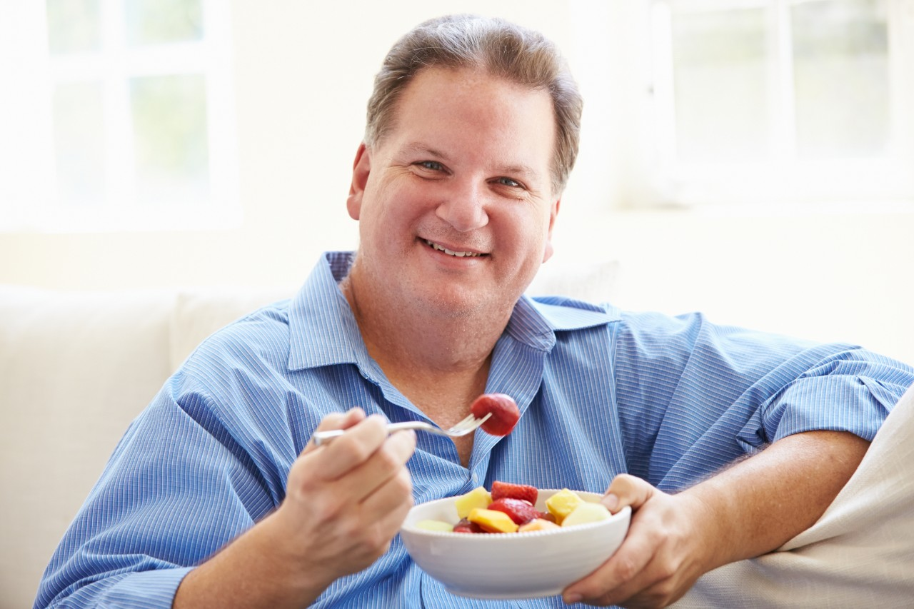 Overweight man eating fresh fruit.
