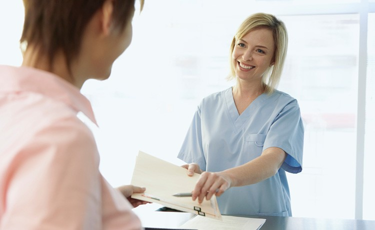Nurse hands paperwork to patient