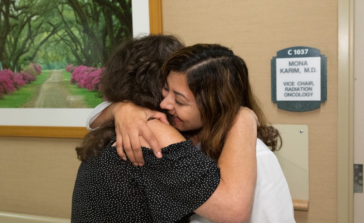 radiation oncologist hugging patient after treatment