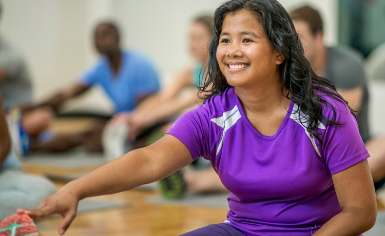 Woman stretches in fitness class