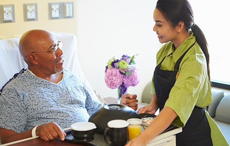 Hospital patient receiving meal during stay