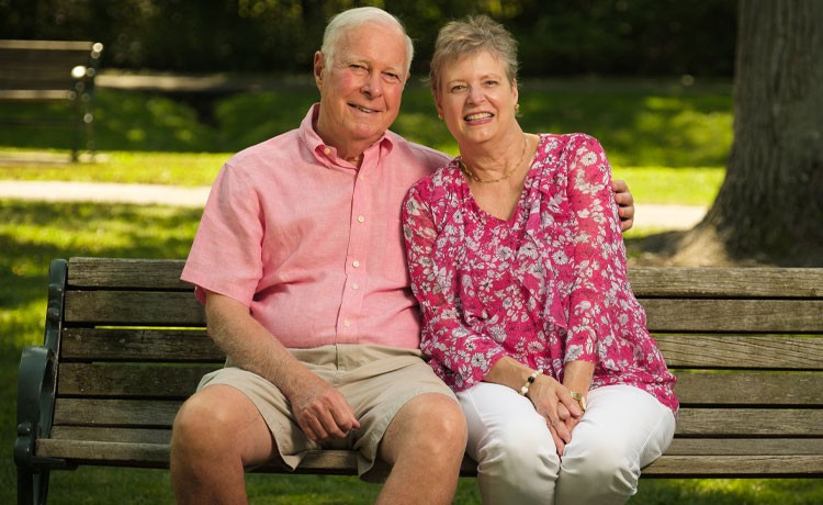 Former DBS patient sits on park bench with husband